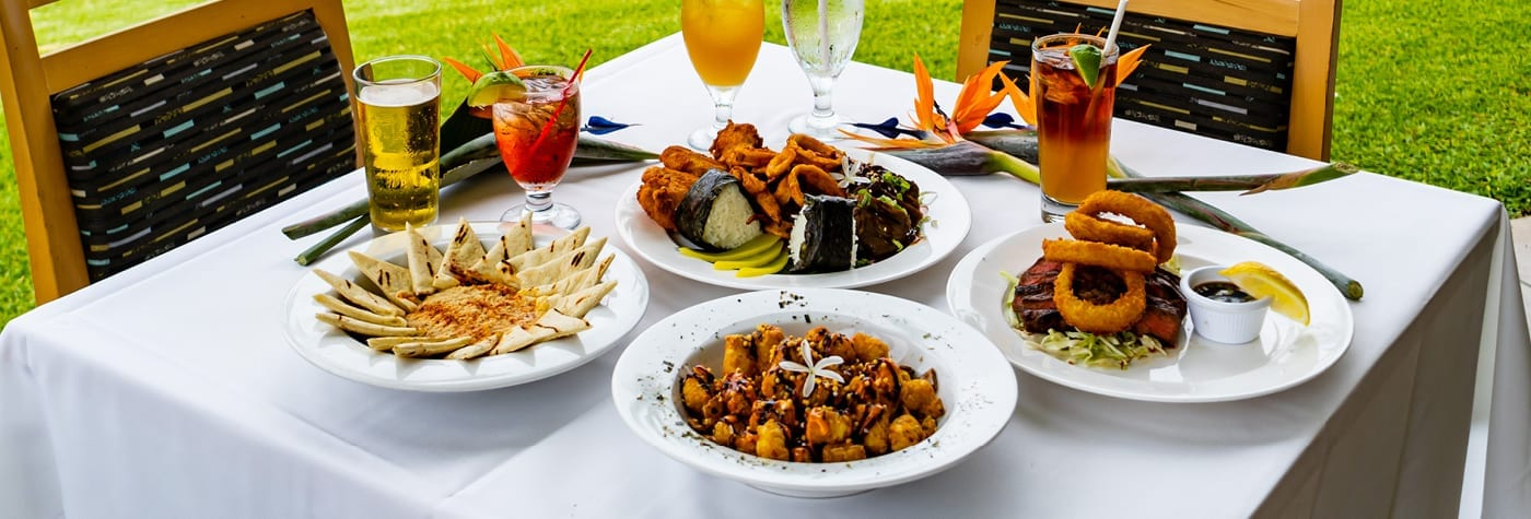 Bird of Paradise - Outdoor dining table with food and drinks.