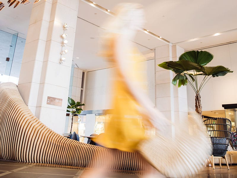 Blurry image of a woman walkingt through the lobby.