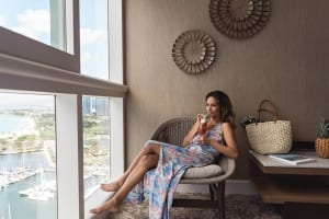 Photo of a Woman Relaxing in a Sizable Guest Room. Combine Work and Travel This Spring at Prince Waikiki.