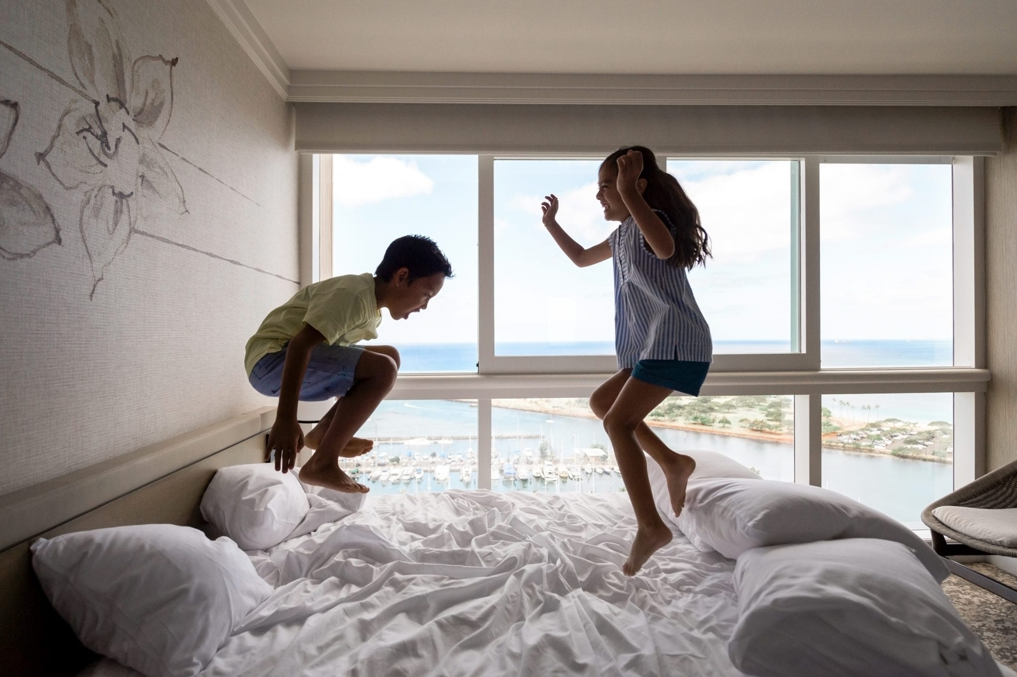 Children jumping on a bed.