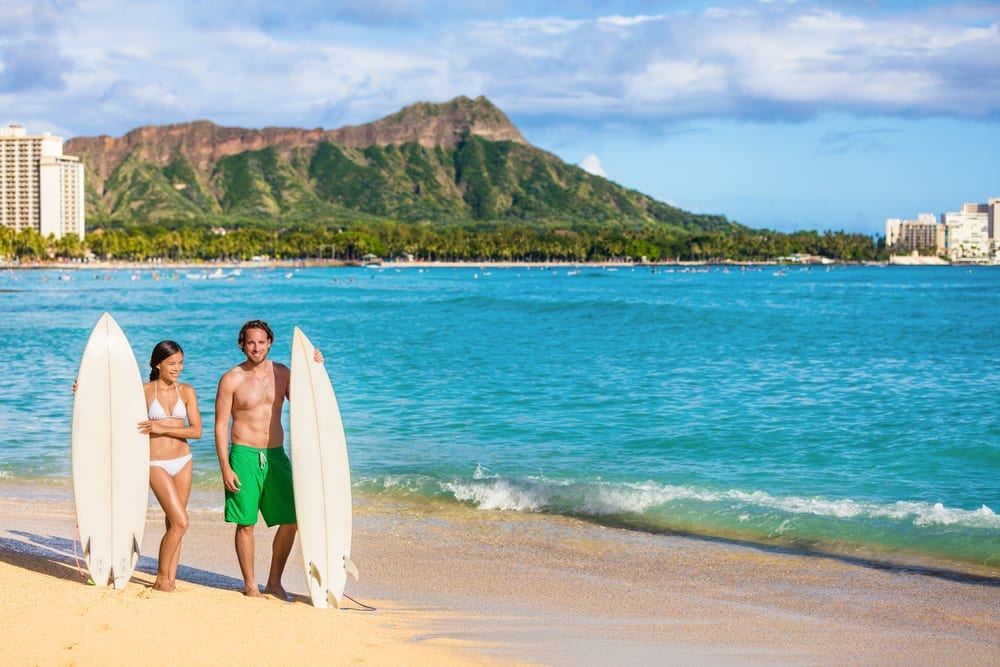 Couple on beach with surfboards.