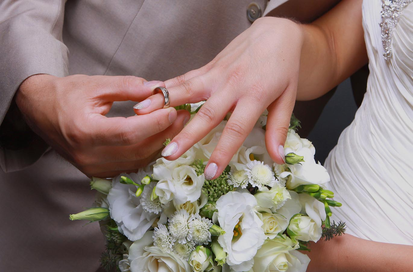 Close up of groom placing a ring on a bride's finger.