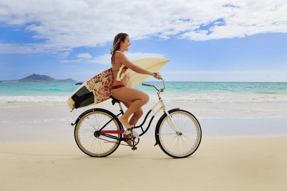 Woman biking on the beach with a surfboard.