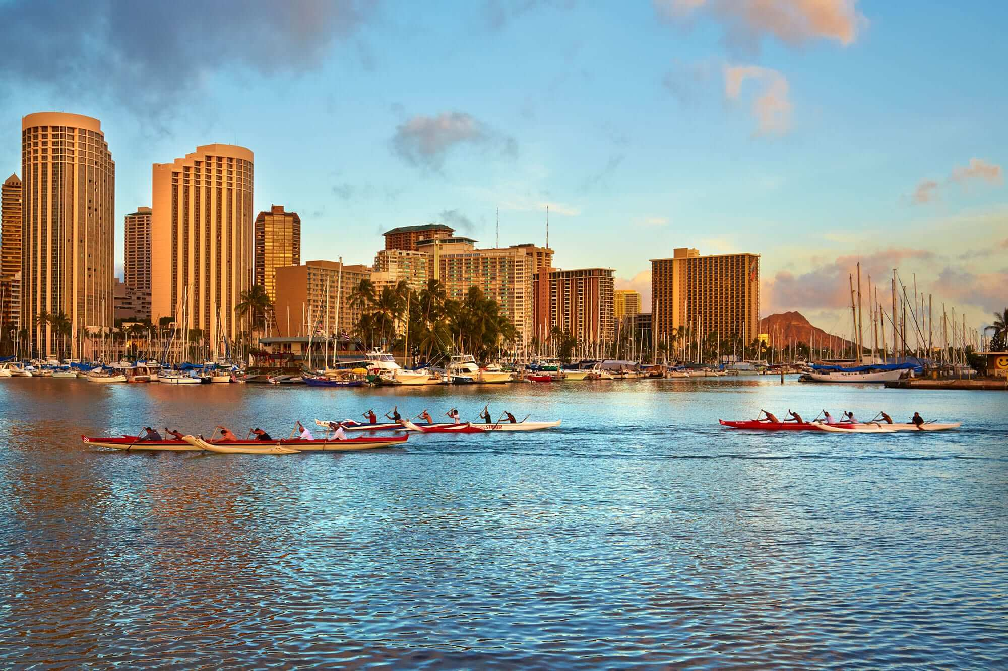Outrigger boats traveling across the bay in front of Prince Waikiki.