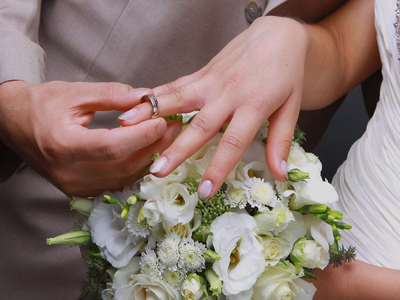 Close up of bride with wedding ring and bouquet.