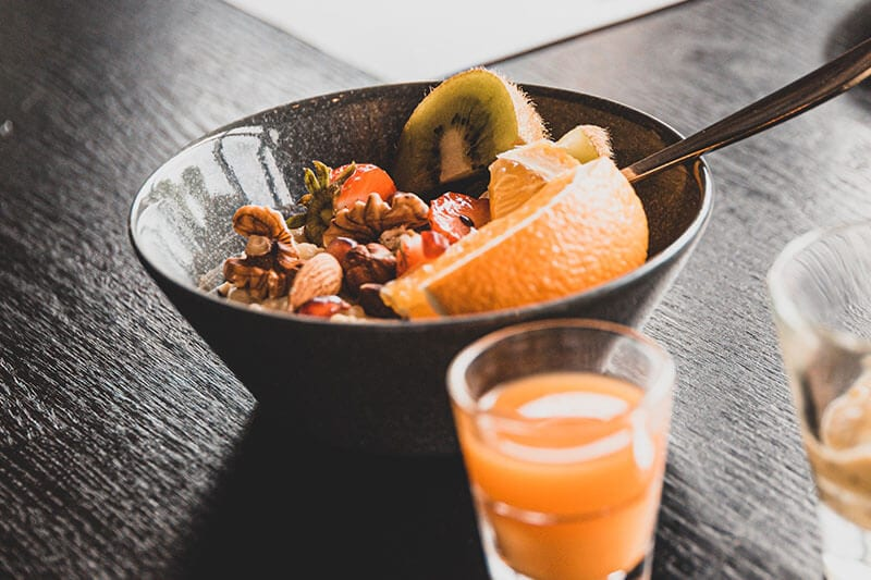 Breakfast bowl of fruit and grains with orange juice.