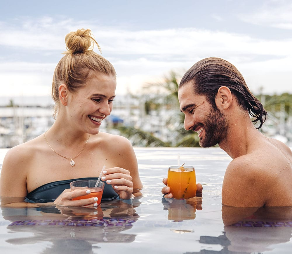 Couple in the pool with drinks.