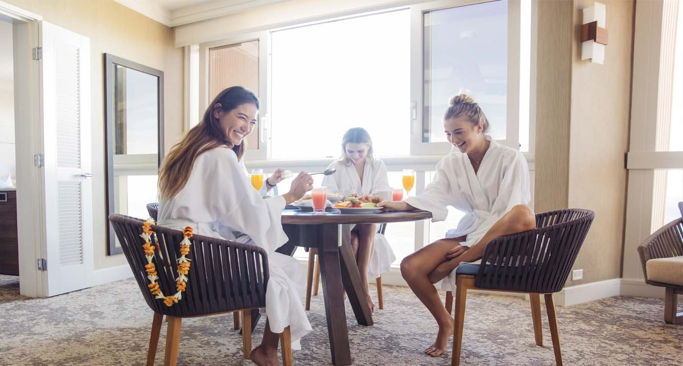 Women having brunch in robes.