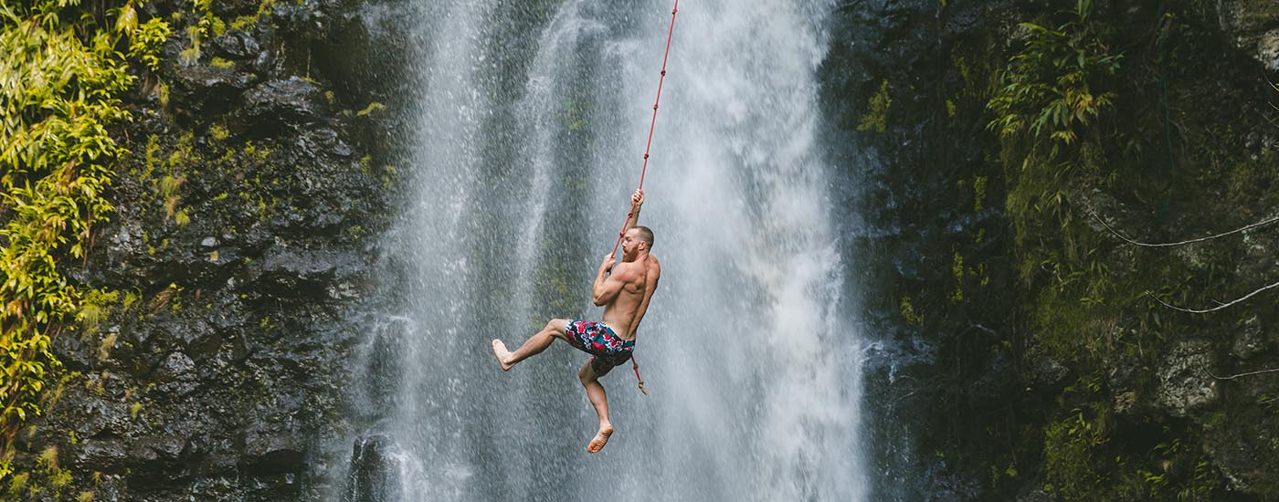 Man swinging on a rope by a waterfall.