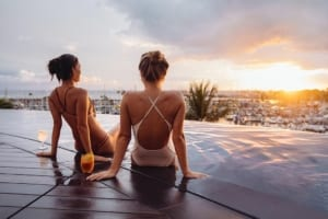 Photo of Two Women Beside an Infinity Pool after a Day of Parasailing in Waikiki