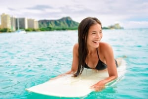 Photo of a Woman Surfing near Waikiki Beach, One of the Most Beloved Recreational Activities.