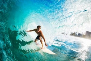 Photo of a Man Surfing in Waikiki. Click Here for Ideas on How to Stay Fit on Vacation.