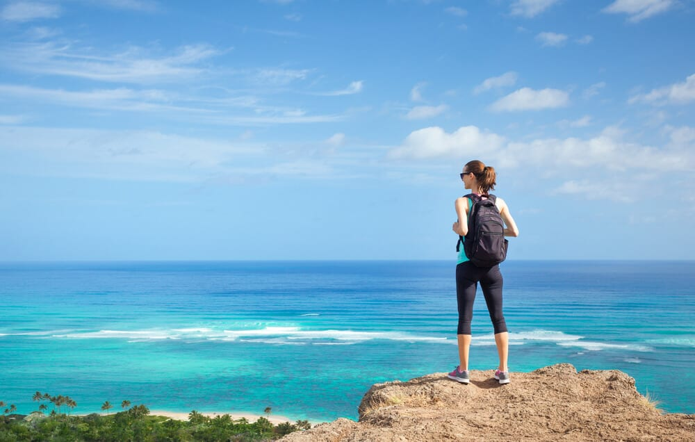 Photo of a Woman Hiker Looking at the Pacific Ocean in Oahu. Click Here for Ideas on How to Stay Fit on Vacation.