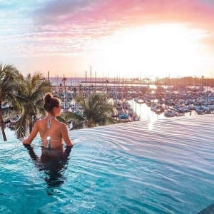 Photo of a Woman Soaking in Prince Waikiki's Infinity Pool at Dusk. Click Here for 10 Oahu Hidden Gems.