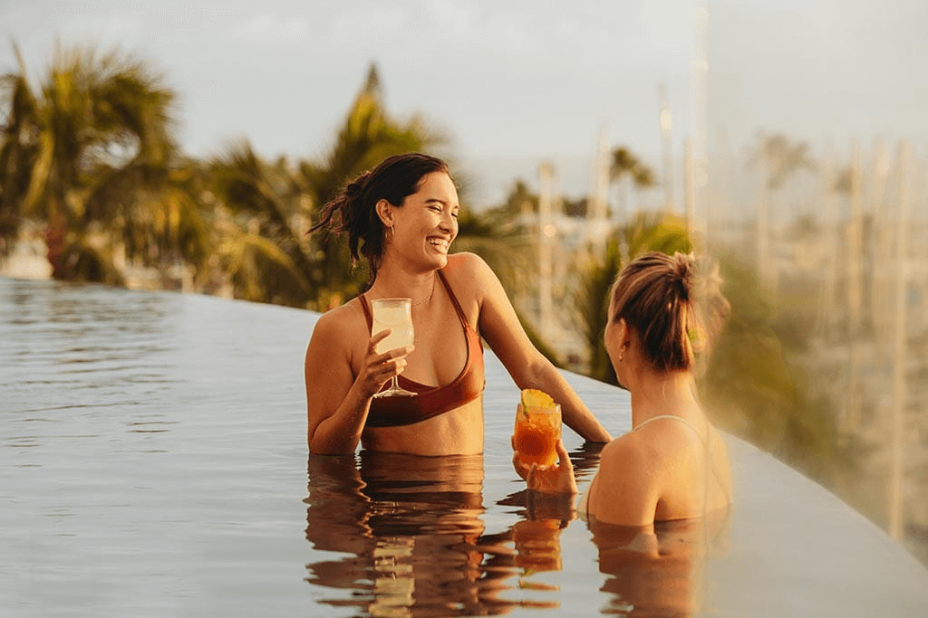 A picture of two women holding drinks in a pool during a Kamaaina staycation