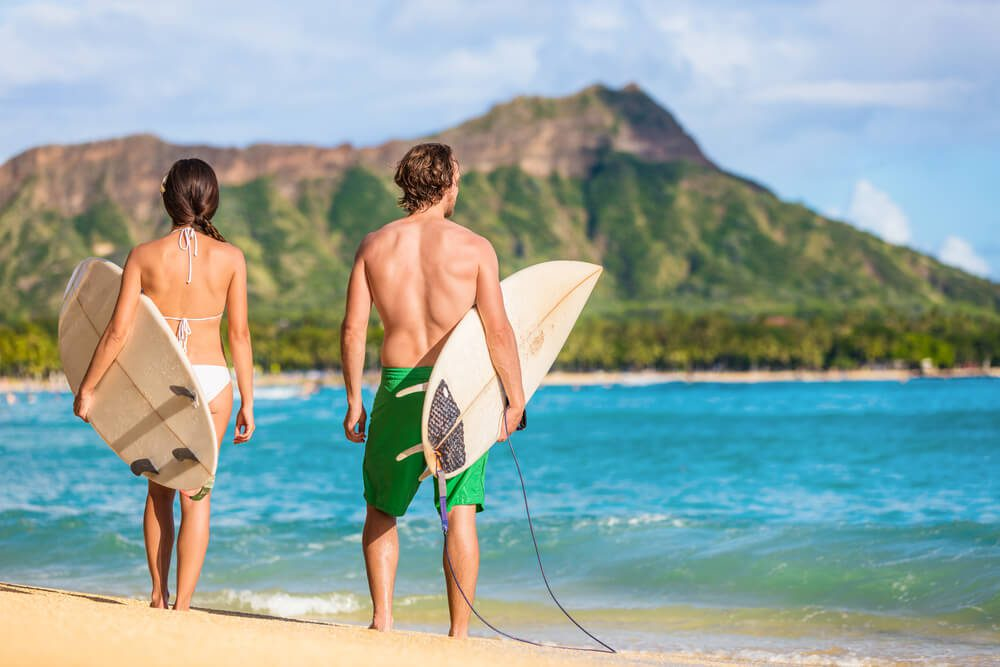 A photo of a couple in Waikiki with rental surfboard.